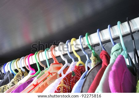 Rows of colorful clothes hanger in wardrobe. - stock photo