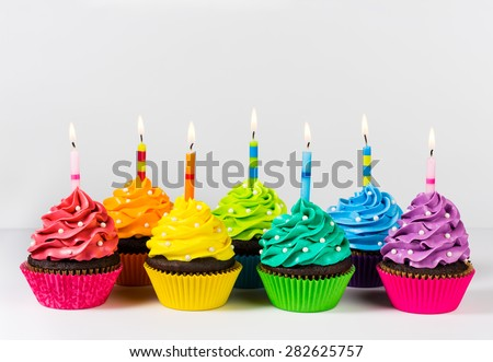 Rows of colourful cup cakes decorated with birthday candles and sprinkles. - stock photo