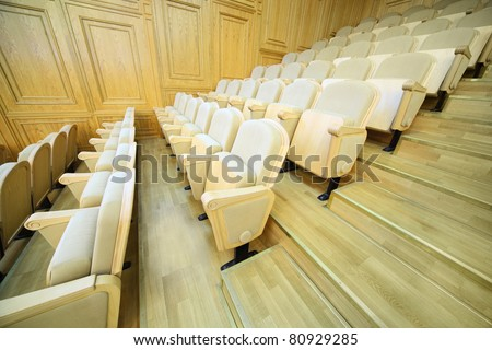 Rows of comfortable beige folding chairs inside big light hall - stock photo