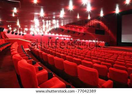 Rows of comfortable red chairs in illuminate red room cinema - stock photo