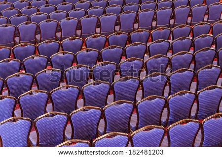 Rows of empty comfortable wooden chairs arranged in neat rows in an entertainment venue or auditorium, full frame background view slightly angled - stock photo