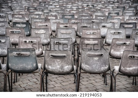 Rows of empty plastic seats on stone pavement, outdoor setting - stock photo