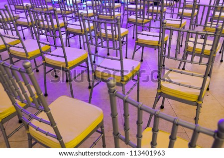 Rows of event chairs for guests and audience bathe in purple stage lights - stock photo