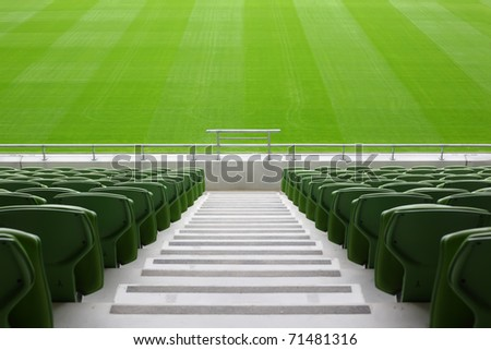 Rows of folded, green, plastic seats in very big, empty stadium - stock photo