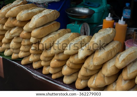 Rows of fresh bread loafs lying on the shelf to prepare for sale in the market, Delicious ! Paneled French baguette separated into layers of preparation - stock photo