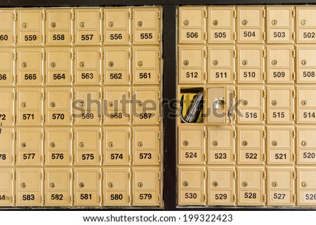 Rows of gold post office boxes with one open mail box. - stock photo