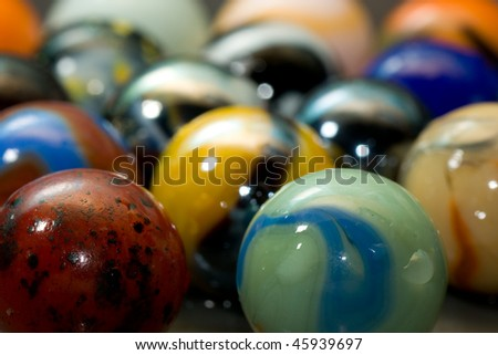 Rows of muliti colored marbles wet with water - stock photo