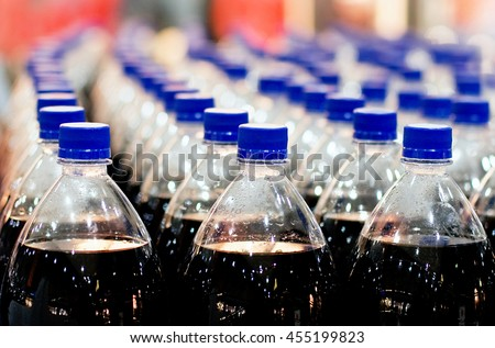 Rows of plastic bottles in the store, inside - stock photo
