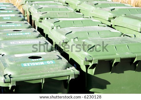 Rows of recycle bins lined up outdoors - can also represent environmental issues, responsibility, etc. (shallow focus). - stock photo