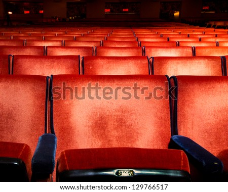 Rows of red velvet theater seats - stock photo