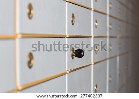 Rows of safety deposit boxes in a bank vault or security lockers with a receding perspective and a key in the lock of one of the doors - stock photo