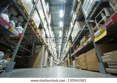 Rows of shelves with boxes and other goods in modern warehouse - stock photo