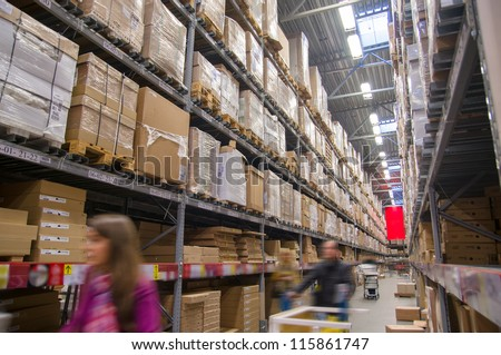 Rows of shelves with boxes in modern warehouse with customers walking - stock photo