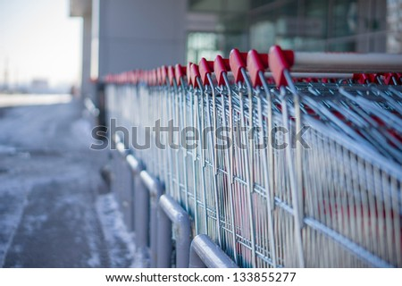 Rows of shopping carts on entrance of supermarket - stock photo