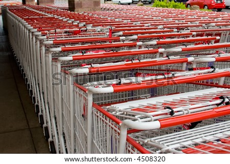 Rows of shopping carts outside waiting to be used - stock photo
