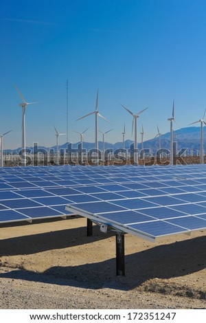 Rows of solar panels and wind turbines capture the sun and wind. - stock photo