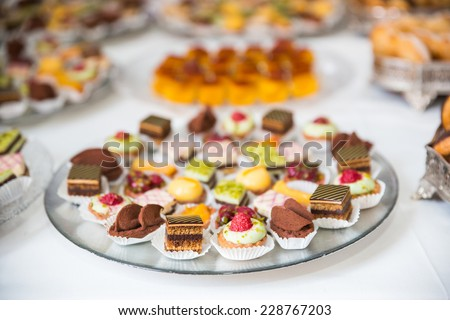 Rows of tasty looking desserts in beautiful arrangements. Sweets on banquet table - picture taken during catering event - stock photo