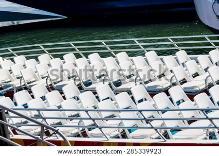 Rows of white seats on the open deck of a ferry - stock photo