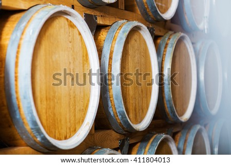 Rows of wine barrels in vaults at the winery. - stock photo