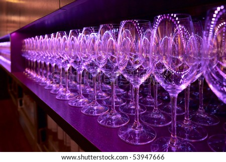 Rows of wineglasses illuminated with blue lamps - stock photo