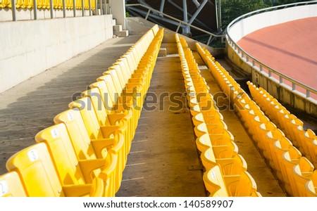 Rows of yellow football stadium. - stock photo