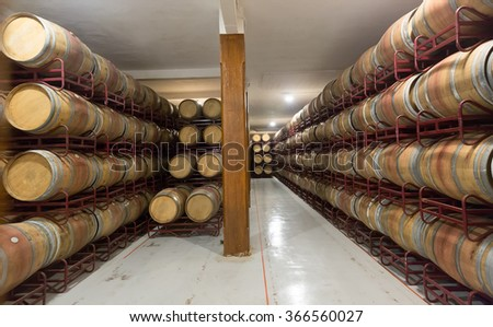 Rows with wooden barrels in  winery factory  - stock photo