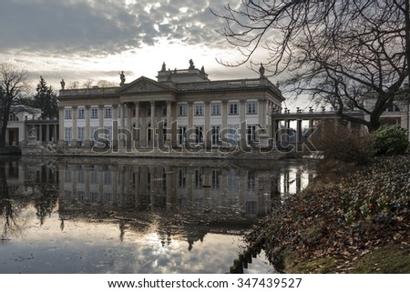 Royal Baths in Warsaw. Palace and pond with reflecting in the building. A thin sheet of ice water. - stock photo