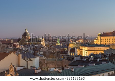 Royal castle and Old Town seen from the Town Hall tower in Krakow, Poland in the evening - stock photo