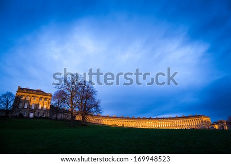 Royal Crescent in Bath, lit by the warm evening light with a stormy looking sky. - stock photo