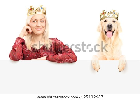 Royal female and dog wearing crowns and posing behind blank panel, isolated on white background - stock photo