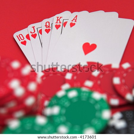Royal flush & casino chips on red - shallow dof - stock photo