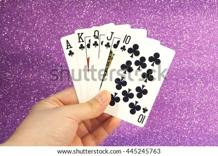 Royal flush club, Playing cards in hand isolated in purple background - stock photo