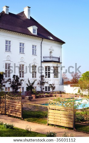 royal palace or manor house. queen margrethe of denmark summer residence Marselisborg castle in Aarhus. view of private swimming pool and facade - stock photo