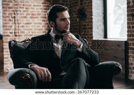 Royalty in his blood. Thoughtful young handsome man in formalwear and bow tie looking away and holding hand on chin while sitting in a chair in loft interior - stock photo