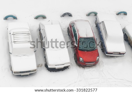 Rub cars completely covered with snow and one red car partially dug out on parking in the city yard during snowfall. - stock photo