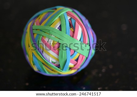 Rubber Band Ball on black surfers. concept photo copyspace - stock photo