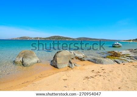 rubber boat and rocks in Porto Pollo beach, Sardinia - stock photo