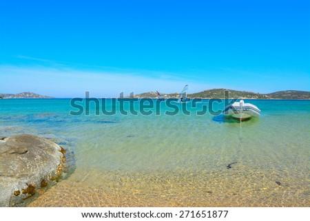 rubber boat and surfers in Porto Pollo, Sardinia - stock photo