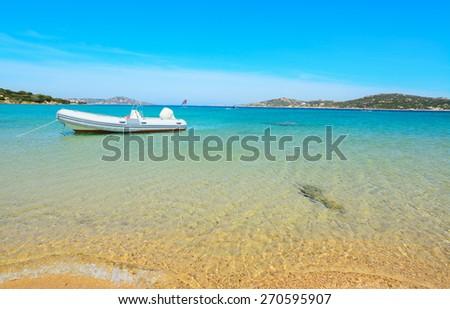 rubber boat moored by the shore in Porto Pollo, Sardinia - stock photo
