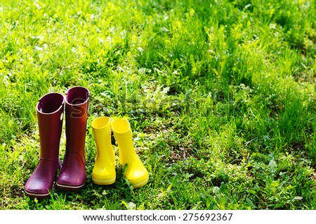 Rubber boots for woman and child in summer garden  - stock photo
