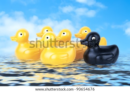 Rubber Duckies floating on water with blue sky - stock photo