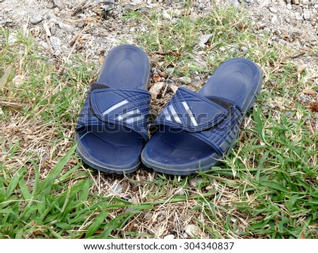 Rubber flip flops slide sandals men on ground - stock photo