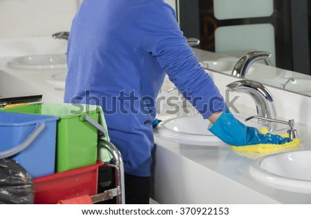 Rubber gloved hand cleaning sink with duster - stock photo