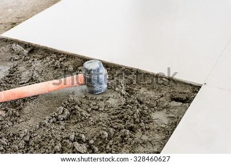 Rubber hammer on floor tile installation for house building - stock photo