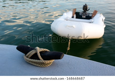 Rubber inflatable dinghy boat towed to a boat. - stock photo