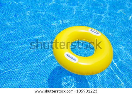 rubber ring floating in transparent blue tiled pool - stock photo