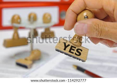 rubber stamp in hand marked with yes - stock photo