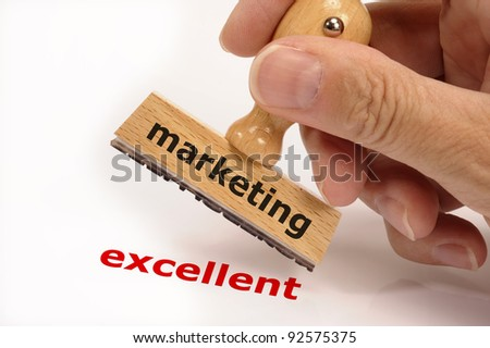rubber stamp marked with marketing in hand and its copy excellent - stock photo