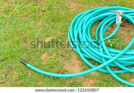 Rubber tube for watering plants in the garden. - stock photo