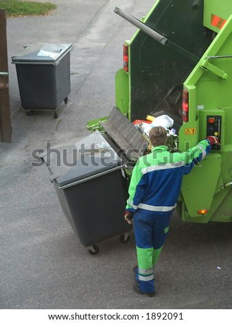 Rubbish collecting machine operator empties boxes, close-up - stock photo